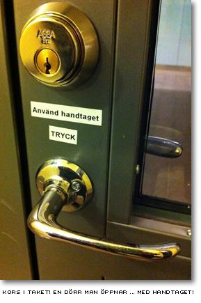 En dörr med lapp som förklarar att man öppnar dörren genom att använda handtaget och trycka