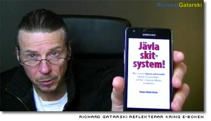Richard Gatarski visar boken i mobiltelefonen