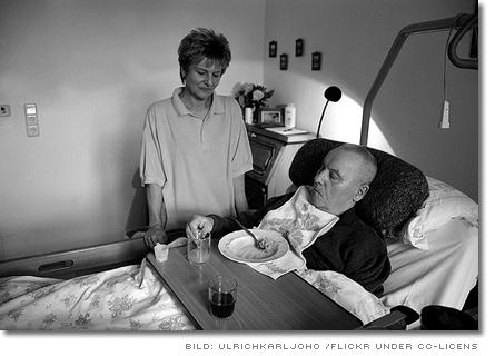 sjuksköterska vid en äldre patient säng