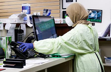 sköterska i skyddsutrustning vid datorskärm